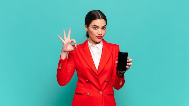 Jonge mooie vrouw die zich gelukkig, ontspannen en tevreden voelt, goedkeuring toont met een goed gebaar, glimlachend. slimme telefoon concept