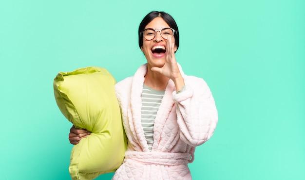 Jonge mooie vrouw die zich gelukkig, opgewonden en positief voelt, een grote schreeuw geeft met handen naast de mond, roept