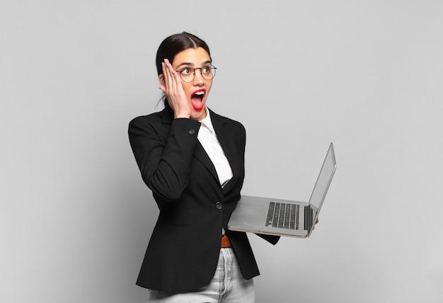 Jonge mooie vrouw die zich gelukkig, opgewonden en verrast voelt, opzij kijkend met beide handen op het gezicht. laptopconcept