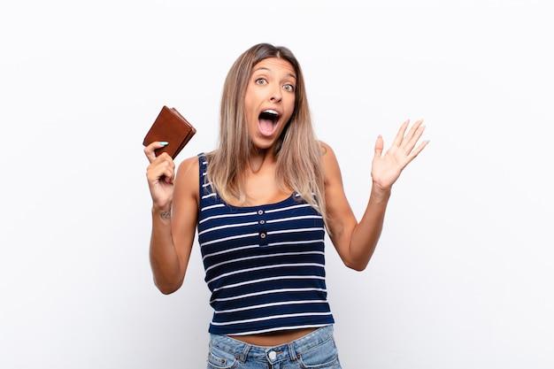 Jonge mooie vrouw die zich gelukkig, opgewonden, verrast of geschokt voelt, glimlacht en verbaasd over iets ongelooflijks met een leren portemonnee.