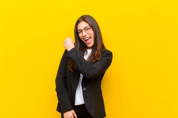 Jonge mooie vrouw die zich gelukkig, positief en succesvol, gemotiveerd voelt wanneer ze voor een uitdaging staat of goede resultaten viert tegen oranje muur