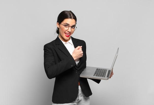 Jonge mooie vrouw die zich gelukkig, positief en succesvol voelt, gemotiveerd wanneer ze voor een uitdaging staat of goede resultaten viert. laptopconcept