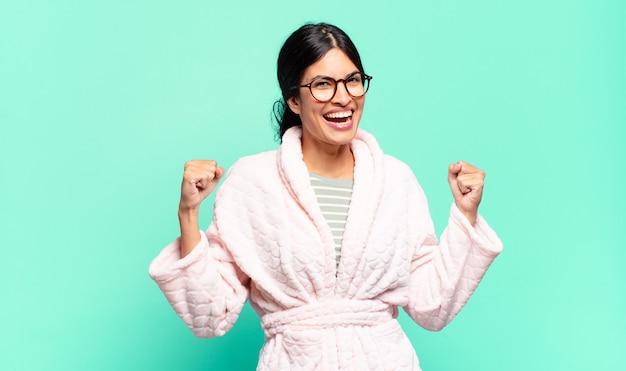 Jonge mooie vrouw die zich gelukkig, positief en succesvol voelt, overwinning, prestaties of veel geluk viert. pyjama's concept