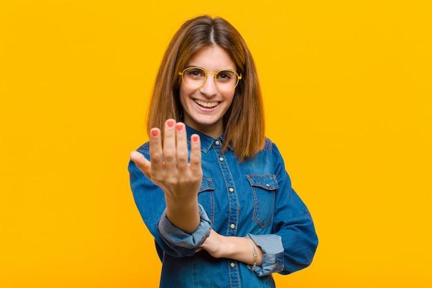 Jonge mooie vrouw die zich gelukkig, succesvol en zelfverzekerd voelt, een uitdaging aangaat en zegt: kom op! of je te verwelkomen tegen de gele muur