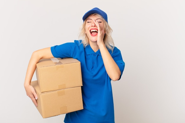 Jonge mooie vrouw die zich gelukkig voelt, een grote schreeuw geeft met de handen naast de mond. pakket leveren concept