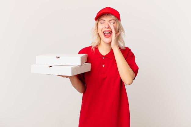 Jonge mooie vrouw die zich gelukkig voelt, een grote schreeuw geeft met de handen naast de mond. pizza bezorgconcept