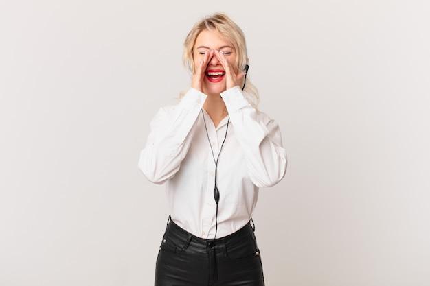 Jonge mooie vrouw die zich gelukkig voelt, een grote schreeuw geeft met de handen naast de mond. telemarketing concept