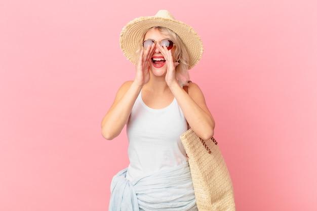 Jonge mooie vrouw die zich gelukkig voelt, een grote schreeuw geeft met de handen naast de mond. zomer toeristische concept