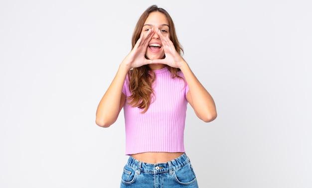 Jonge mooie vrouw die zich gelukkig voelt, een grote schreeuw geeft met de handen naast de mond