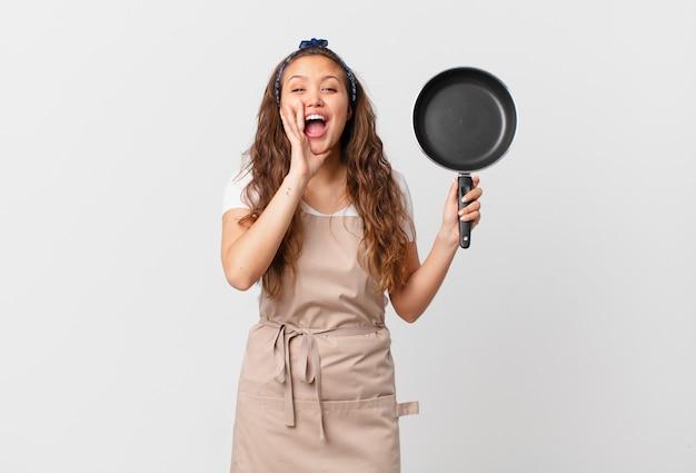 Jonge mooie vrouw die zich gelukkig voelt, een grote schreeuw geeft met de handen naast het concept van de mondchef-kok en een pan vasthoudt