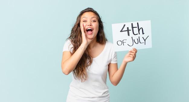 Jonge mooie vrouw die zich gelukkig voelt, een grote schreeuw geeft met de handen naast het concept van de onafhankelijkheidsdag van de mond