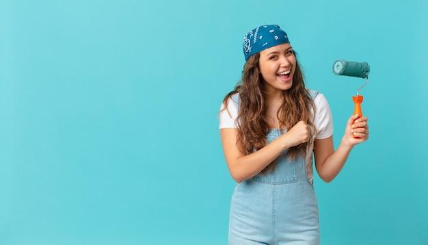 Jonge mooie vrouw die zich gelukkig voelt en een uitdaging aangaat of een muur viert en schildert