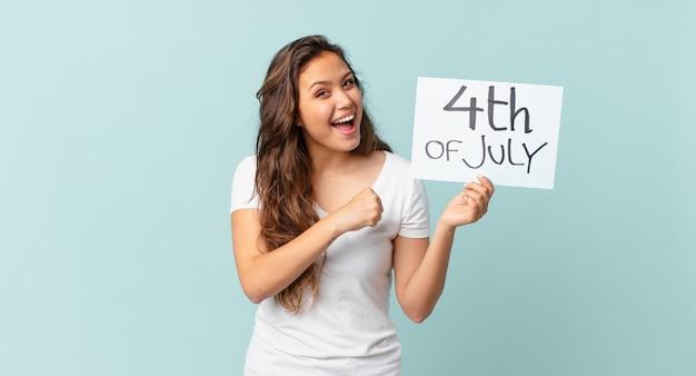 Jonge mooie vrouw die zich gelukkig voelt en een uitdaging aangaat of het concept van de onafhankelijkheidsdag viert