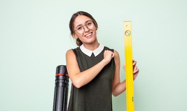 Jonge mooie vrouw die zich gelukkig voelt en een uitdaging aangaat of viert. architectuur concept