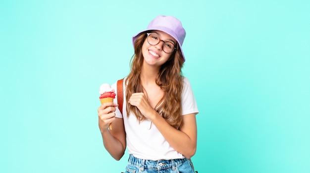 Jonge mooie vrouw die zich gelukkig voelt en een uitdaging aangaat of viert met een ijsje. zomer concept