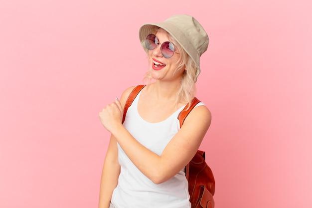 Jonge mooie vrouw die zich gelukkig voelt en een uitdaging onder ogen ziet of viert. zomer toeristische concept