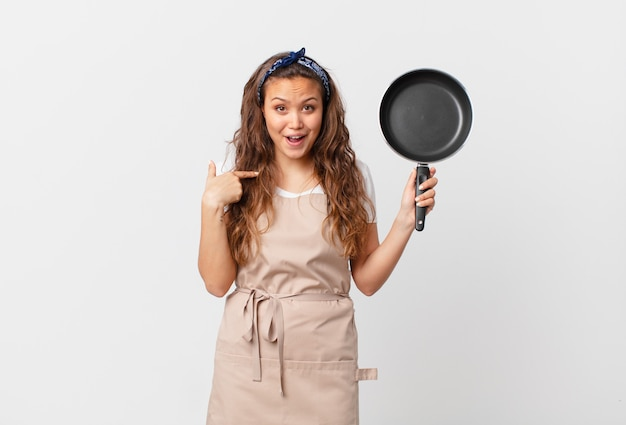 Jonge mooie vrouw die zich gelukkig voelt en naar zichzelf wijst met een opgewonden chef-kokconcept en een pan vasthoudt