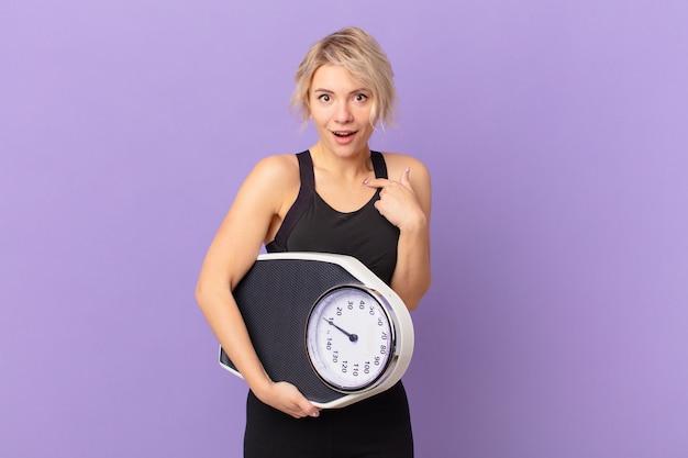 Jonge mooie vrouw die zich gelukkig voelt en naar zichzelf wijst met een opgewonden dieet concept