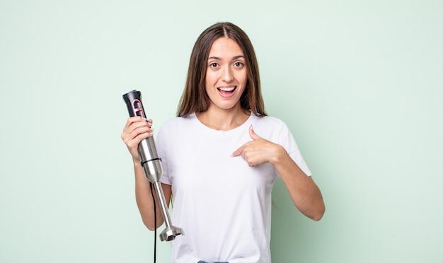 Jonge mooie vrouw die zich gelukkig voelt en naar zichzelf wijst met een opgewonden handmixer concept