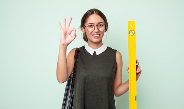 Jonge mooie vrouw die zich gelukkig voelt, goedkeuring toont met een goed gebaar. architectuur concept