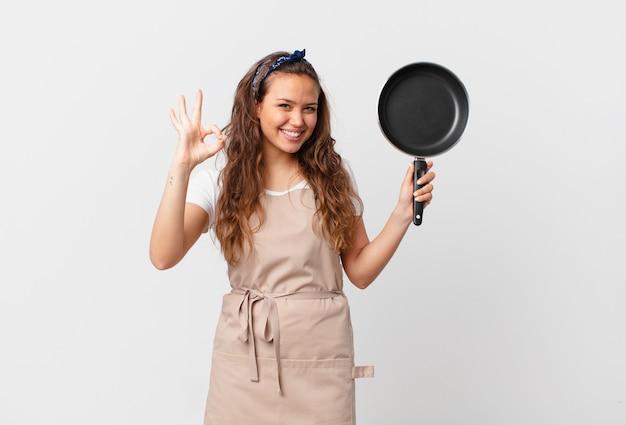Jonge mooie vrouw die zich gelukkig voelt, goedkeuring toont met een goed gebaar chef-kokconcept en een pan vasthoudt