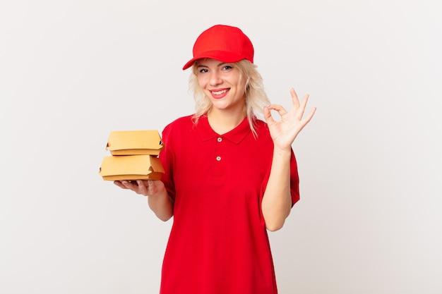 Jonge mooie vrouw die zich gelukkig voelt, goedkeuring toont met een goed gebaar. hamburger bezorgconcept