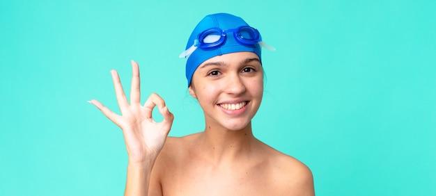 Jonge mooie vrouw die zich gelukkig voelt, goedkeuring toont met een goed gebaar met zwembril