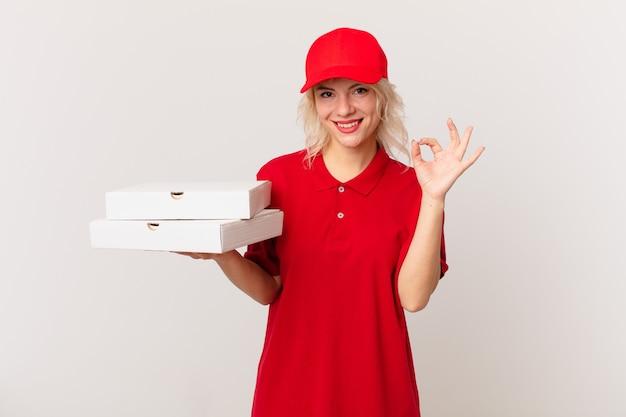 Jonge mooie vrouw die zich gelukkig voelt, goedkeuring toont met een goed gebaar. pizza bezorgconcept
