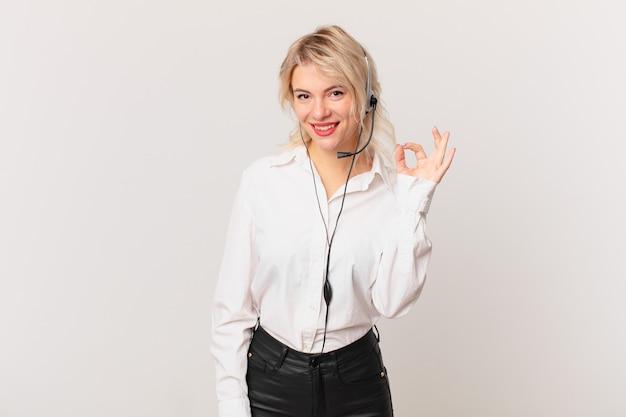 Jonge mooie vrouw die zich gelukkig voelt, goedkeuring toont met een goed gebaar. telemarketing concept