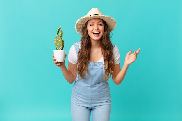 Jonge mooie vrouw die zich gelukkig voelt, verrast een oplossing of idee realiseert en een cactus vasthoudt