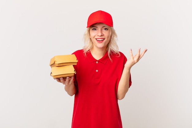 Jonge mooie vrouw die zich gelukkig voelt, verrast en een oplossing of idee realiseert. hamburger bezorgconcept