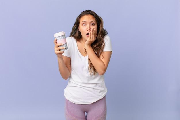 Jonge mooie vrouw die zich geschokt en bang voelt en een kopje koffie vasthoudt