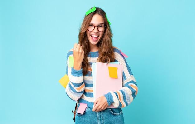 Jonge mooie vrouw die zich geschokt voelt, lacht en succes viert met een tas en boeken vasthoudt