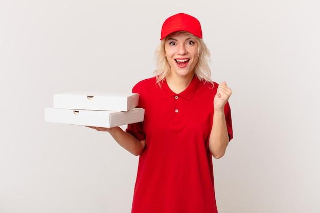 Jonge mooie vrouw die zich geschokt voelt, lacht en succes viert. pizza bezorgconcept