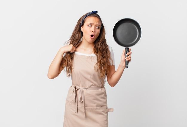 Jonge mooie vrouw die zich gestrest, angstig, moe en gefrustreerd chef-kokconcept voelt en een pan vasthoudt