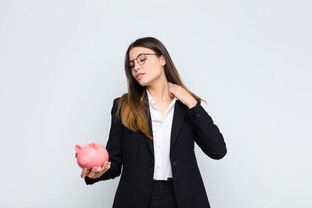 Jonge mooie vrouw die zich gestrest, angstig, moe en gefrustreerd voelt, de hals van het shirt trekt, gefrustreerd kijkt door een probleem met een spaarvarken