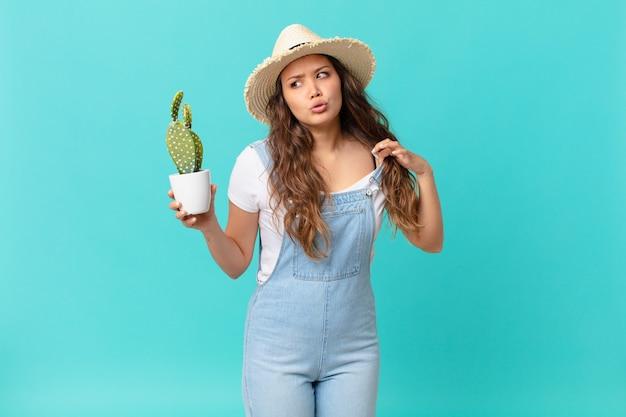 Jonge mooie vrouw die zich gestrest, angstig, moe en gefrustreerd voelt en een cactus vasthoudt