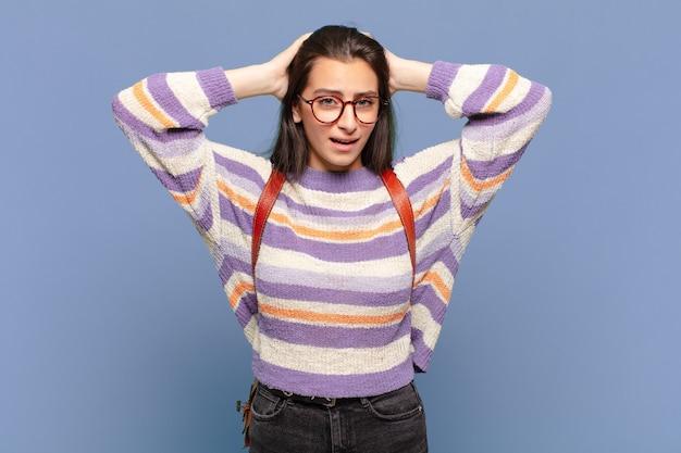 Jonge mooie vrouw die zich gestrest, bezorgd, angstig of bang voelt, met de handen op het hoofd, in paniek bij vergissing. studentenconcept