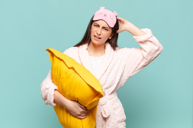 Jonge mooie vrouw die zich gestrest, bezorgd, angstig of bang voelt, met de handen op het hoofd, in paniek bij vergissing. wakker worden met pyjama's concept