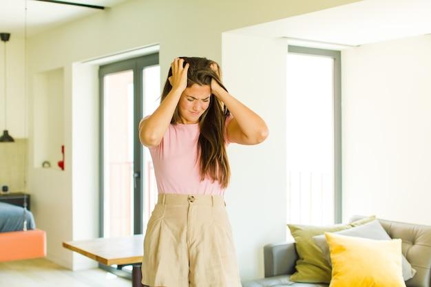 Jonge mooie vrouw die zich gestrest en gefrustreerd voelt, de handen naar het hoofd heft, zich moe, ongelukkig en met migraine voelt