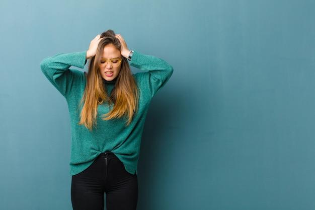 Jonge mooie vrouw die zich gestrest en gefrustreerd voelt, handen opheft, zich moe, ongelukkig en met migraine voelt