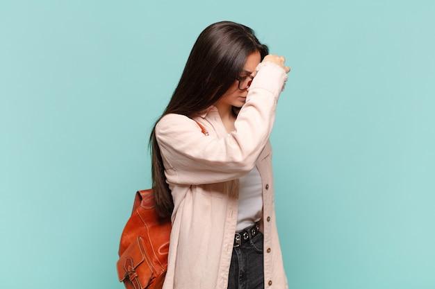 Jonge mooie vrouw die zich gestrest, ongelukkig en gefrustreerd voelt, het voorhoofd aanraakt en lijdt aan migraine of ernstige hoofdpijn. studentenconcept