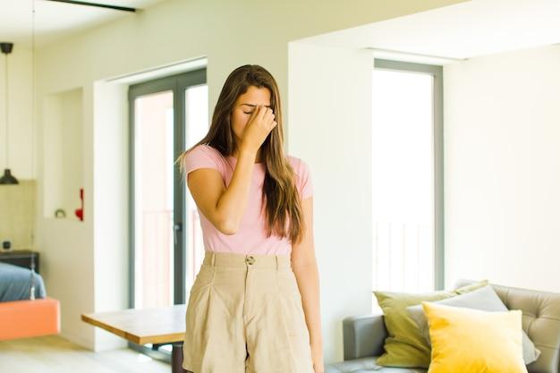 Jonge mooie vrouw die zich gestrest, ongelukkig en gefrustreerd voelt, het voorhoofd aanraakt en lijdt aan migraine of ernstige hoofdpijn