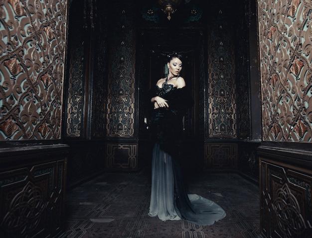 Jonge mooie vrouw die zich in de paleisruimte bevindt
