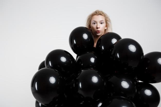 Jonge mooie vrouw die zich in zwarte ballons over witte muur bevindt