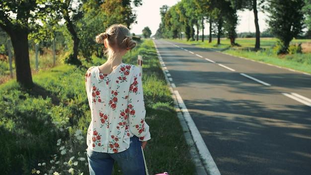 Jonge mooie vrouw die zich op de weg met een koffer bevindt.