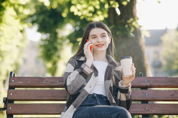 Jonge mooie vrouw die zich op een bank bevindt die de telefoon met behulp van