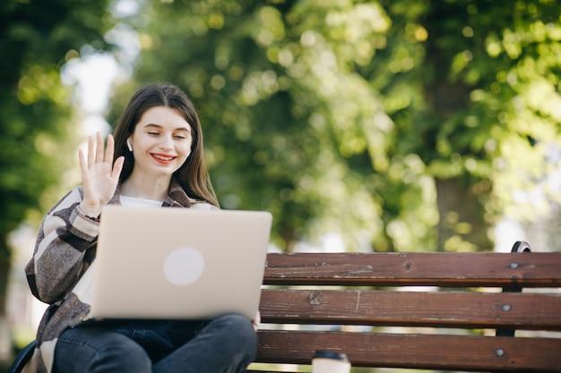 Jonge mooie vrouw die zich op een bank bevindt die laptop met behulp van