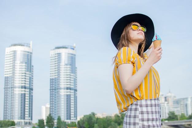 Jonge mooie vrouw die zich op het strand in een geel gestreept t-shirt in oranje glazen en een zwarte hoed en het eten van ijs, wandelen in de zomer buiten de stad