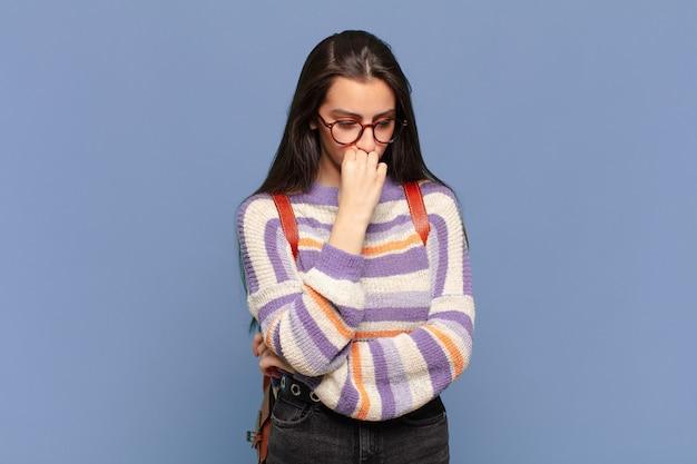 Jonge mooie vrouw die zich serieus, attent en bezorgd voelt, zijwaarts starend met de hand tegen de kin gedrukt. studentenconcept